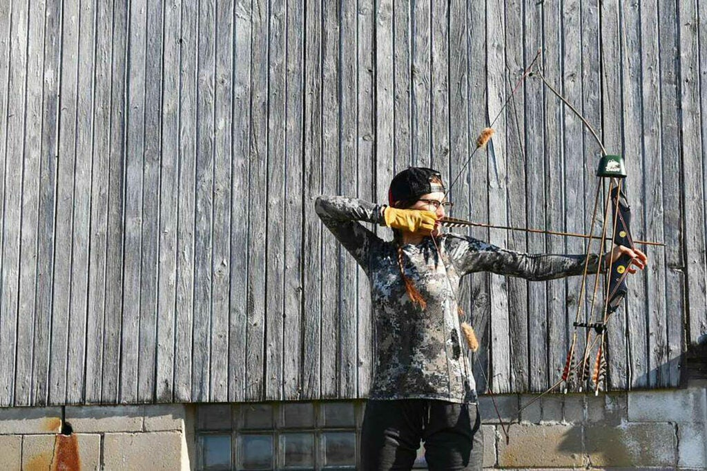 A female archer draws a traditional recurve bow in front of a wooden barn .