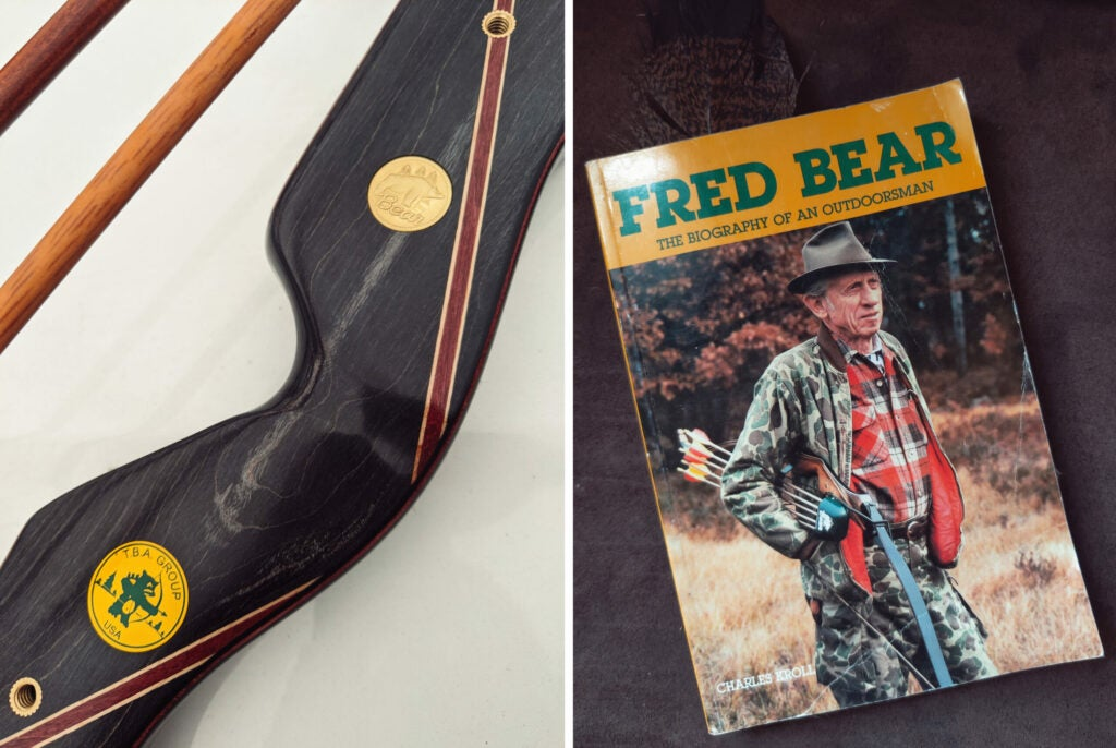 A photograph of a black maple riser on a recurve bow beside an old paperback copy of a Fred Bear biography.