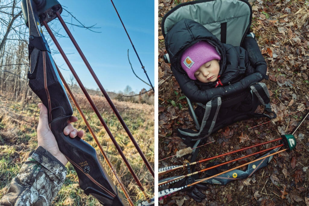 A hand holds up the dark wooden riser of a recurve bow beside a sleeping toddler in a backpack carrier set in the leaves.
