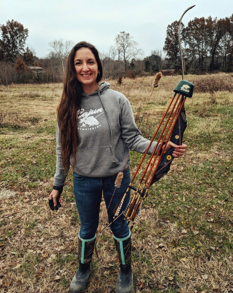 A woman with long hair in a gray hoodie holds a traditional recurve bow with a quiver full of arrows on a gray November day.