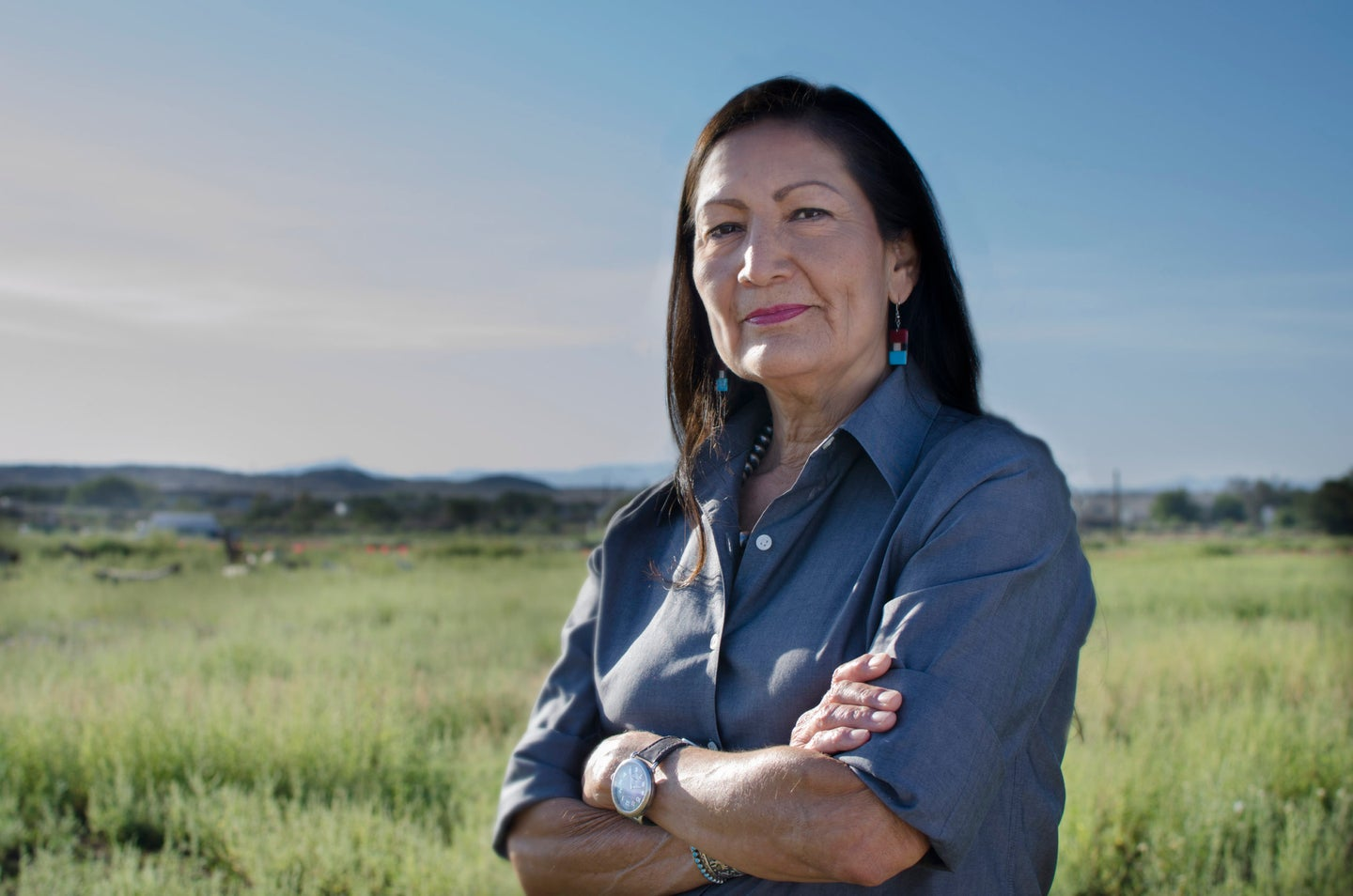 A New Mexican woman with dark hair and turquoise earrings crosses her arms and looks at the camera in an open field.