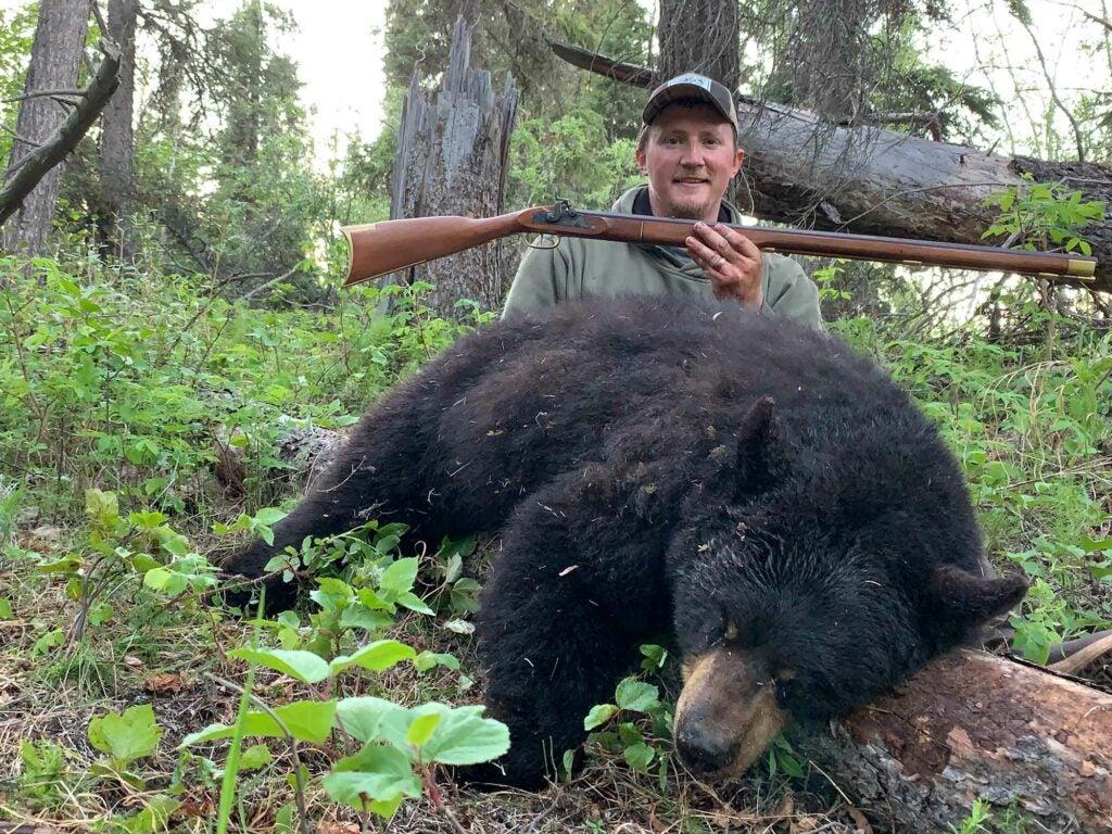 The hunter, Tyler Freel, and black bear with .50-caliber flintlock