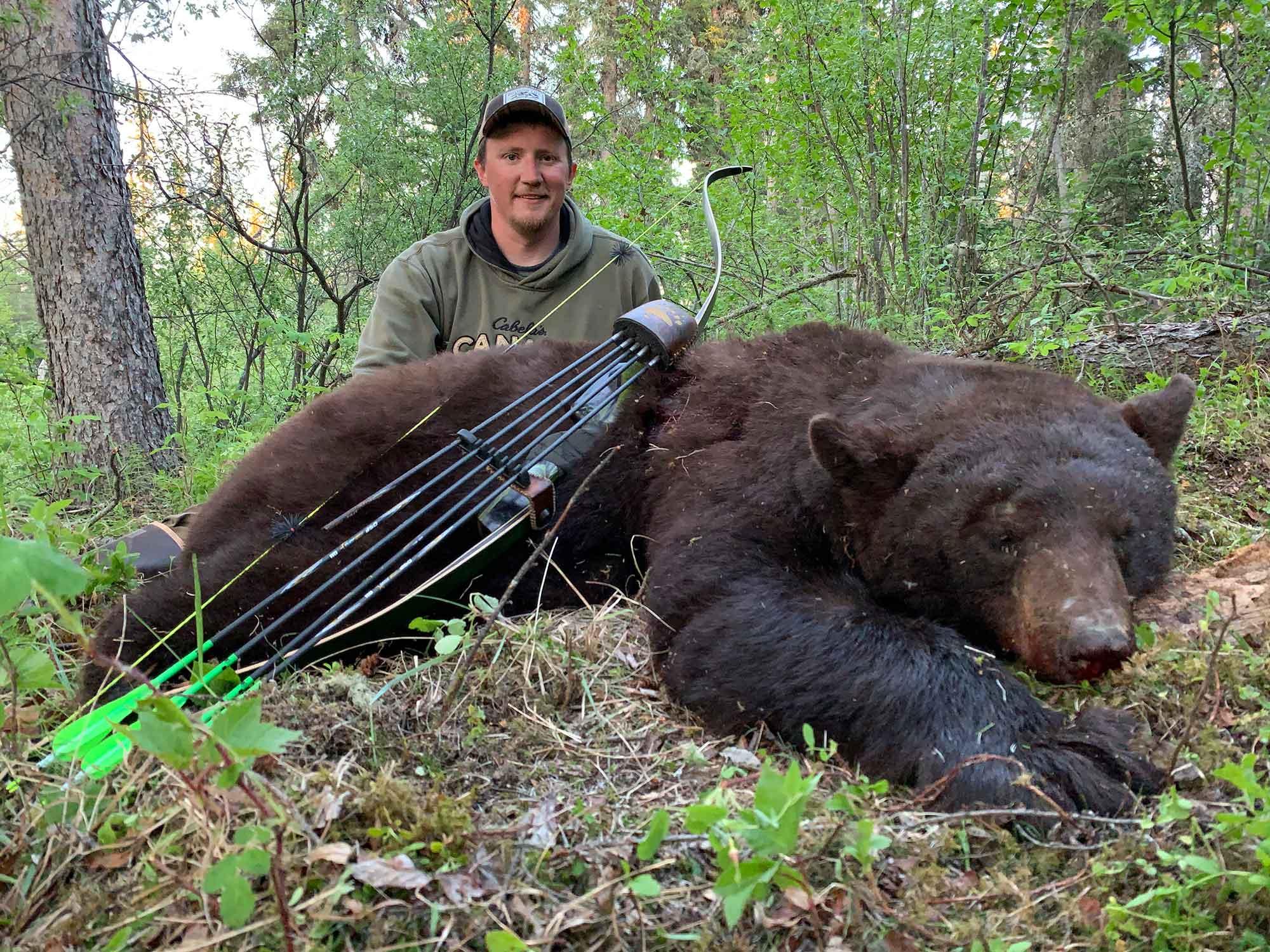 Hunter beside dead bear and bow