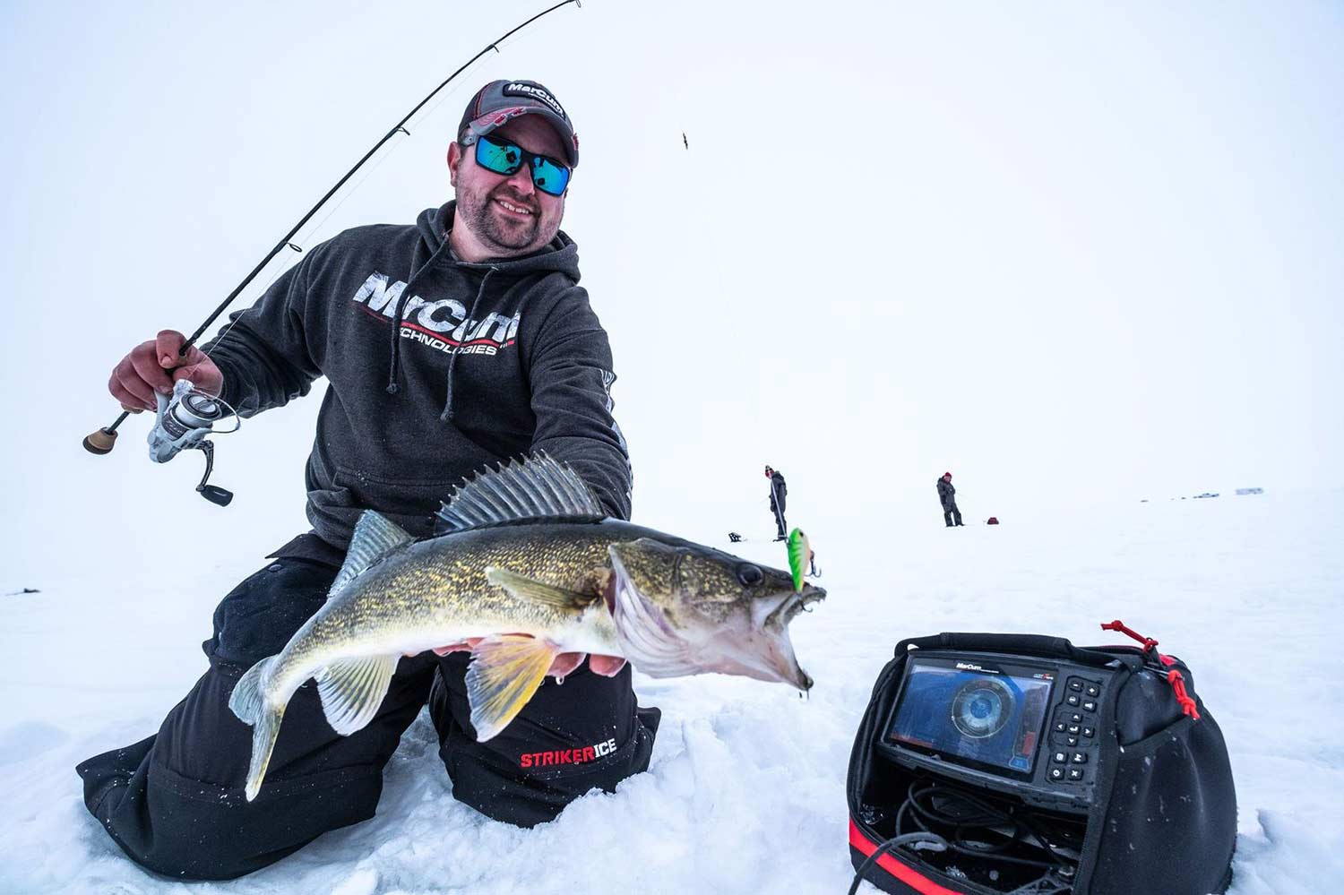 An angler holds a walleye caught from an ice fishing hole.