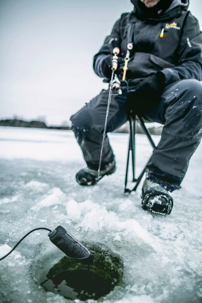 An angler fishes in an ice fishing hole.
