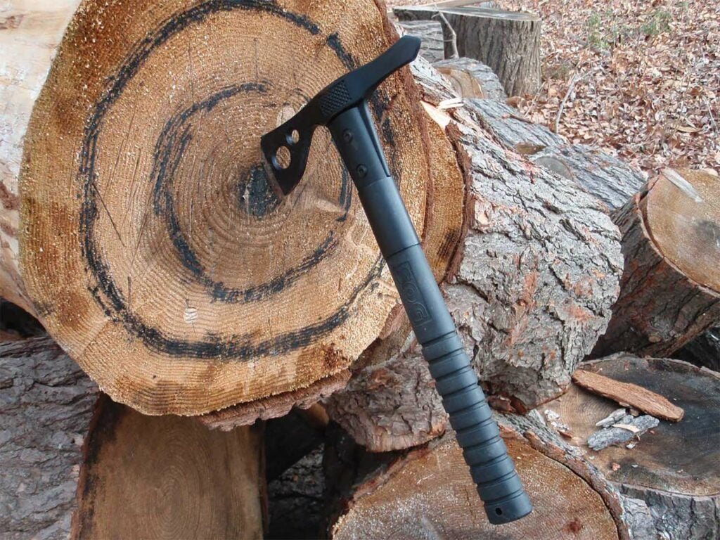 A tactical throwing axe stuck in a tree stump.
