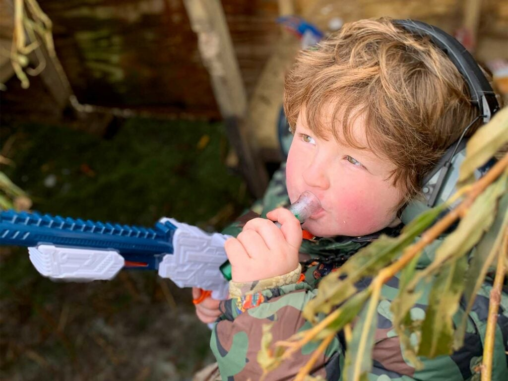 A young kid blows on a duck call while holding a toy gun.