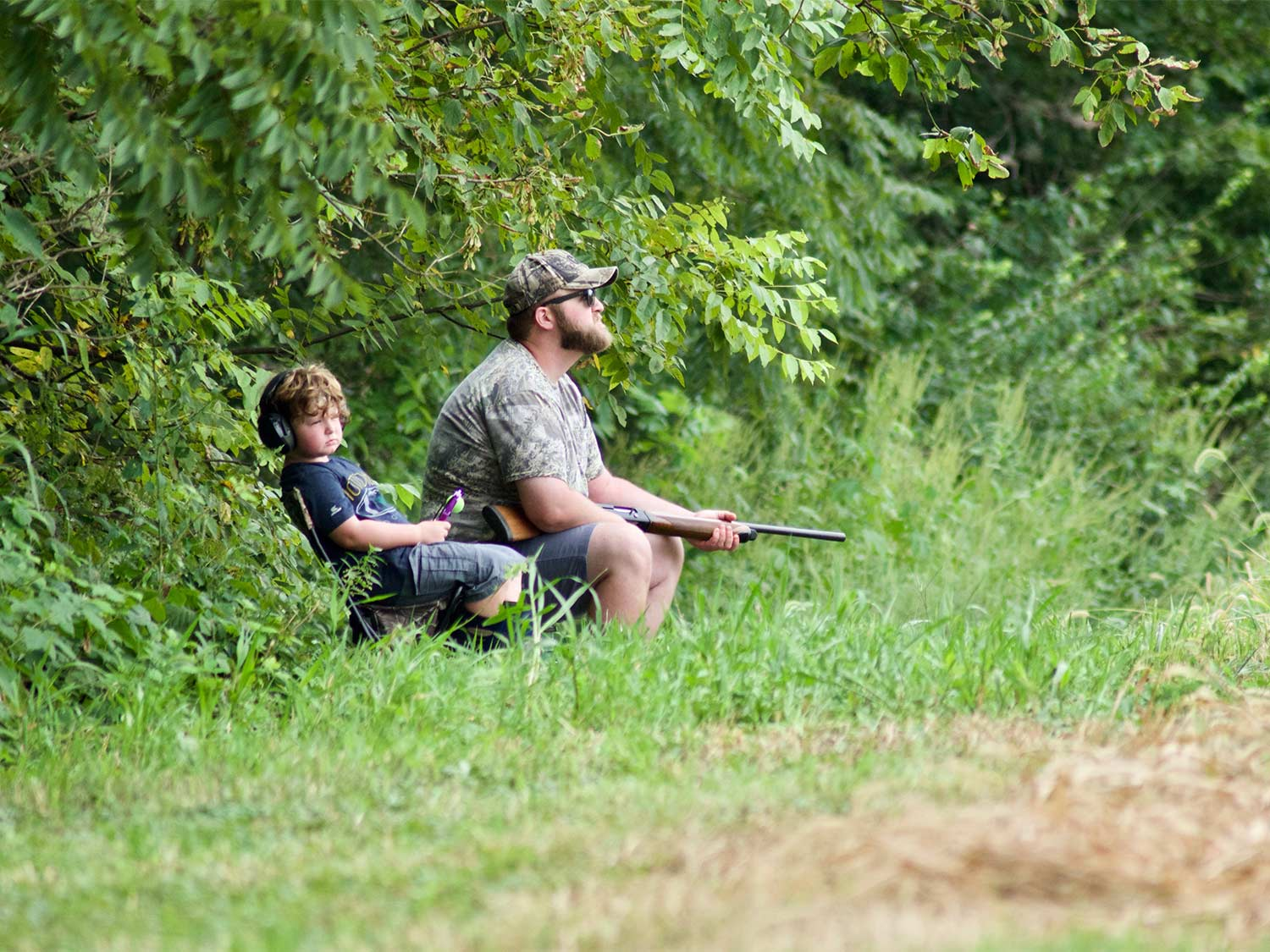 A man and a young kid sit at the edge of a field for hunting.