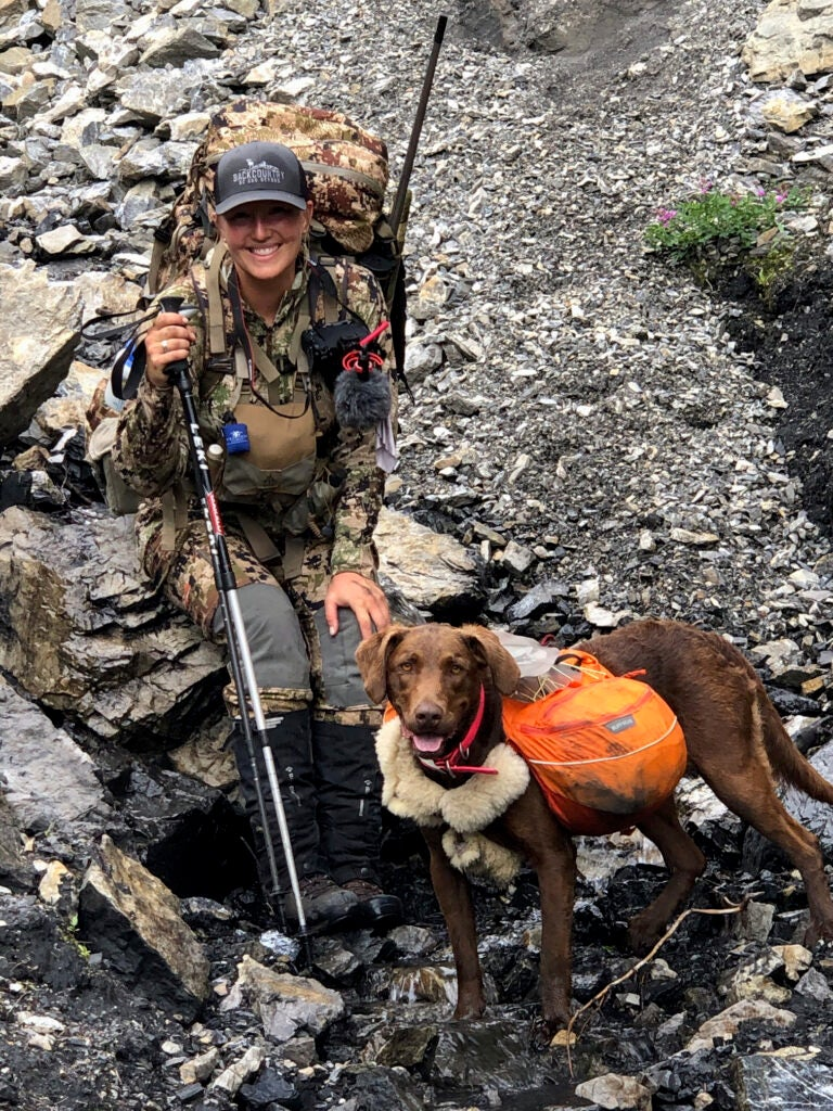 A female big-game guide with trekking poles and a heavy pack rests on a rock beside her dog.