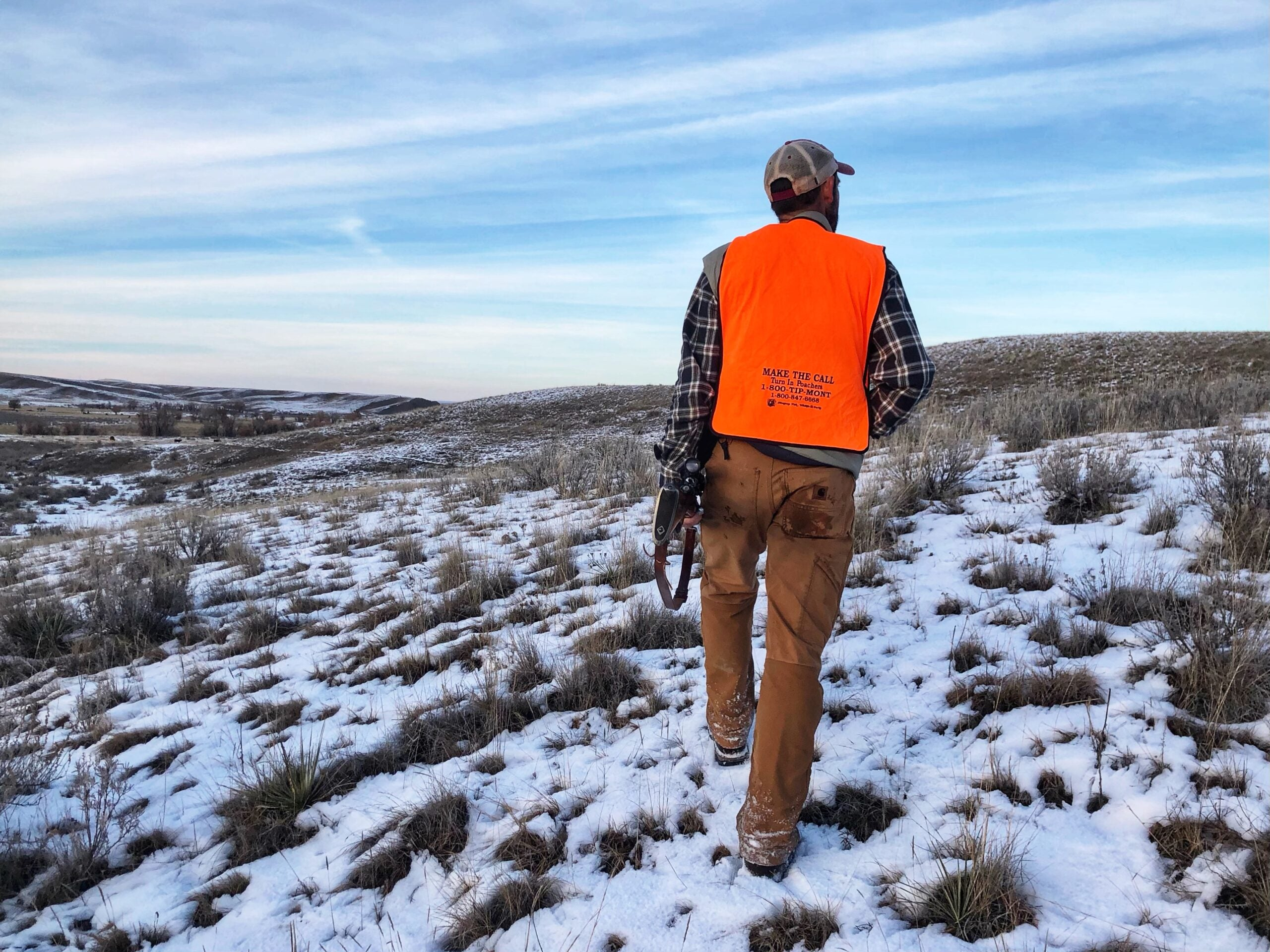 A Western deer hunter in a flannel and blaze orange vest carries a rifle on the Montana prairie.