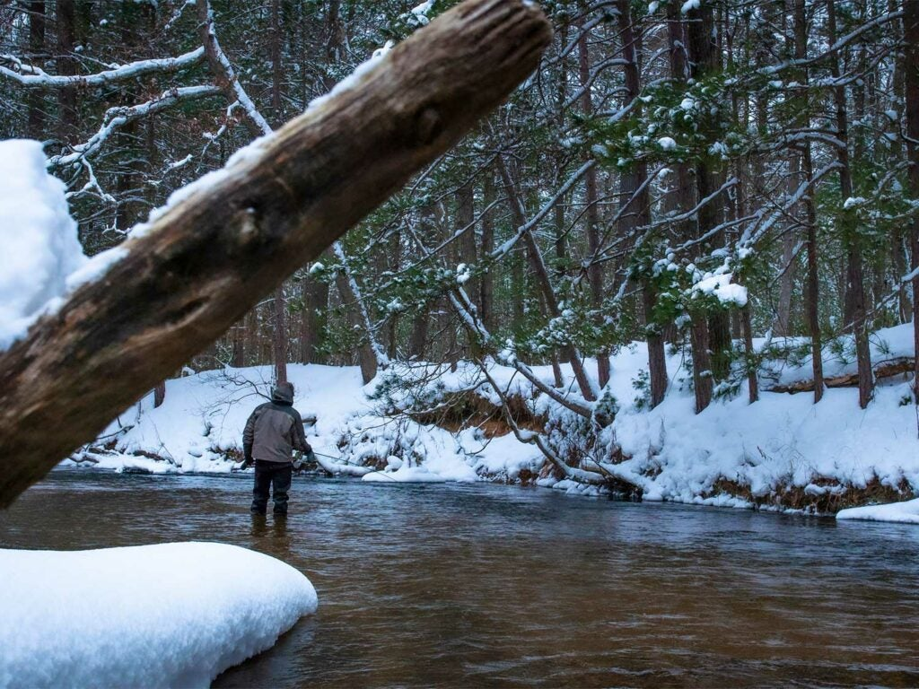 An angler wades into a river and fishes in the snow.