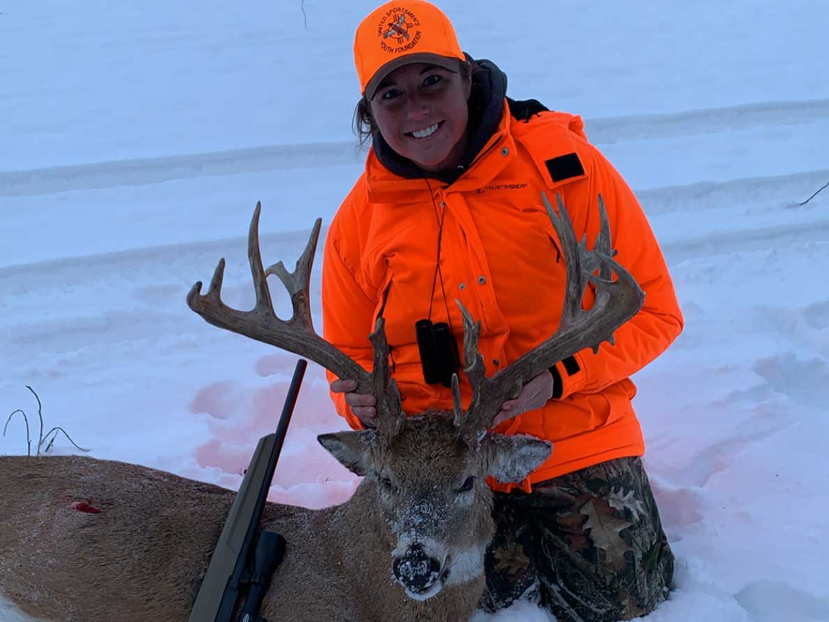 A hunter kneels behind a whitetail deer in the snow.