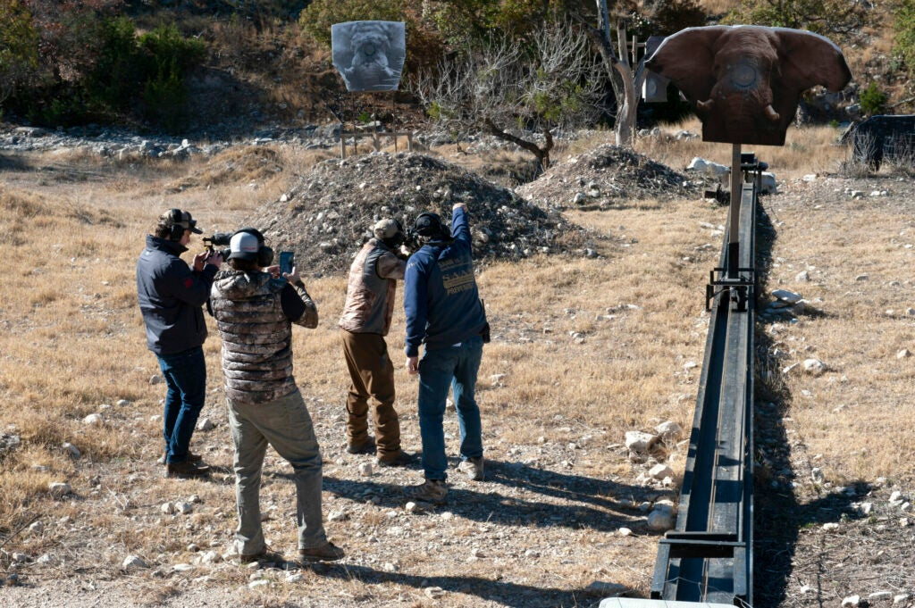 A hunter practices on a charging elephant target with an instructor and two videographers.