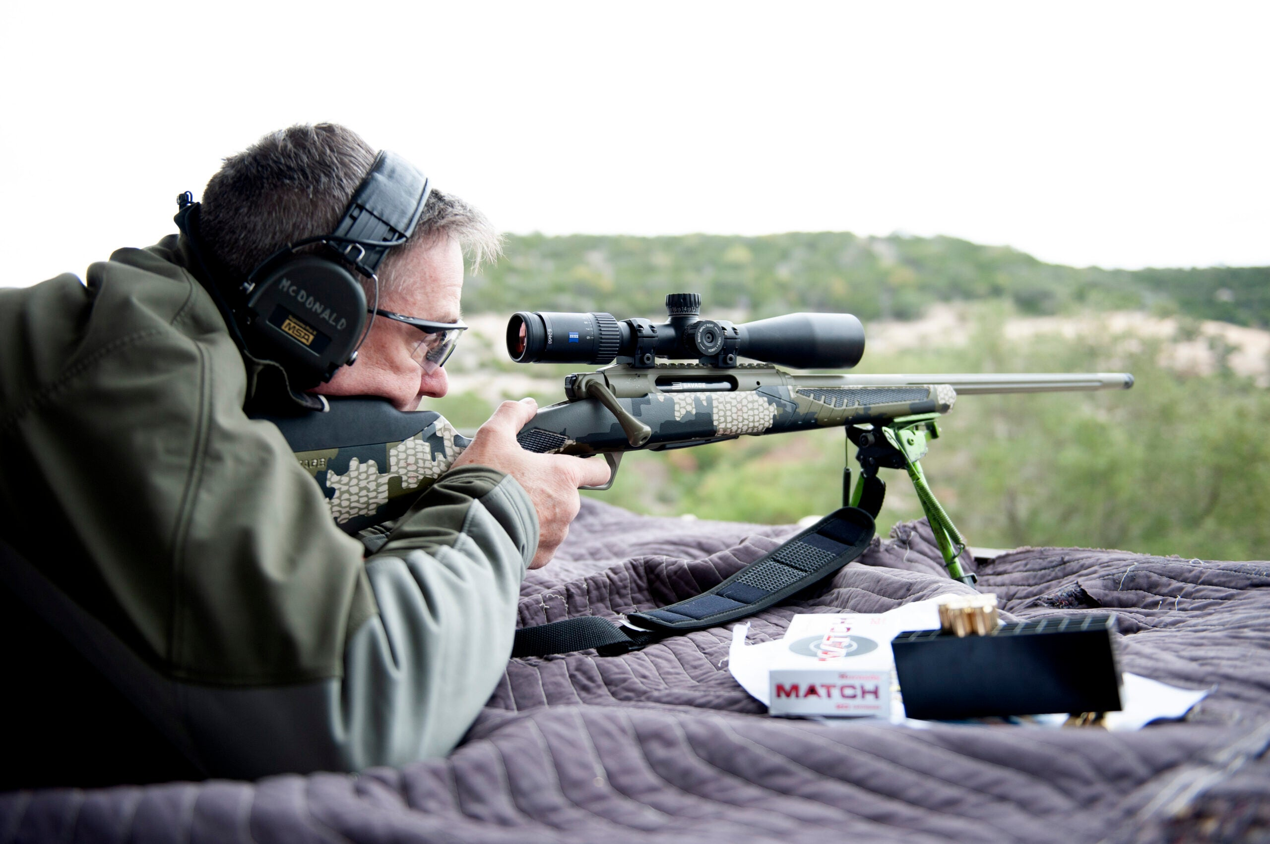 A man with glasses and ear protection lying prone behind a camo rifle on a shooting blanket in rugged country.
