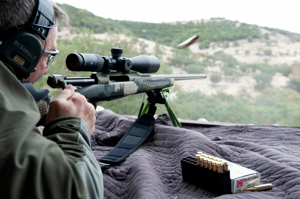 A man cycles a straight-pull rifle action, ejecting a brass cartridge while shooting prone.