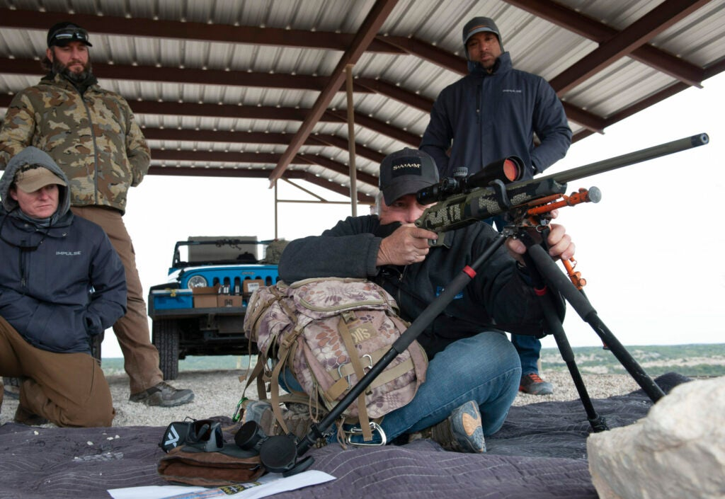 An instructor behind a big-game rifle while  shooting students observe.