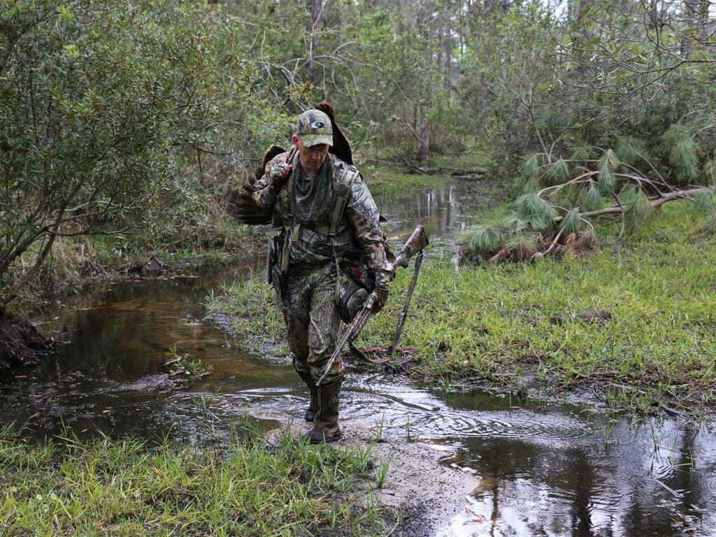 A hunter walks through a small stream while hunting