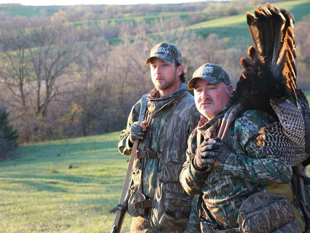Two turkey hunters in a large open field.