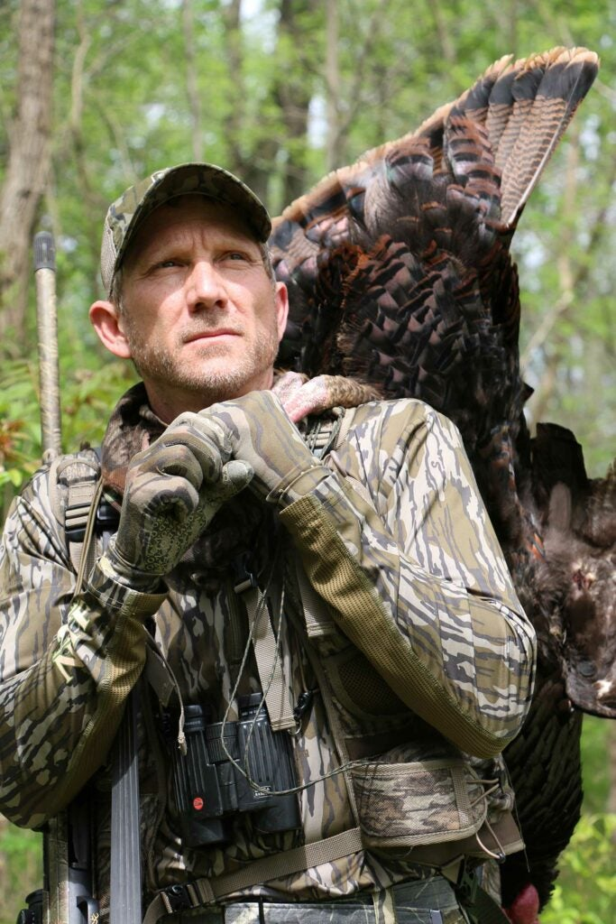 A hunter holds a turkey over his shoulder.