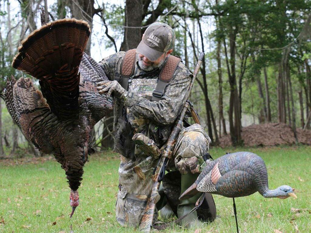 A hunter holds up a turkey next