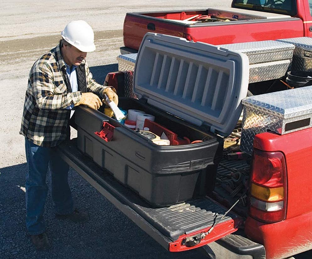 Man opening one of the best storage bins in the back of his truck