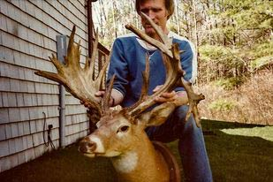 A hunter kneeling behind a large whitetail deer trophy.