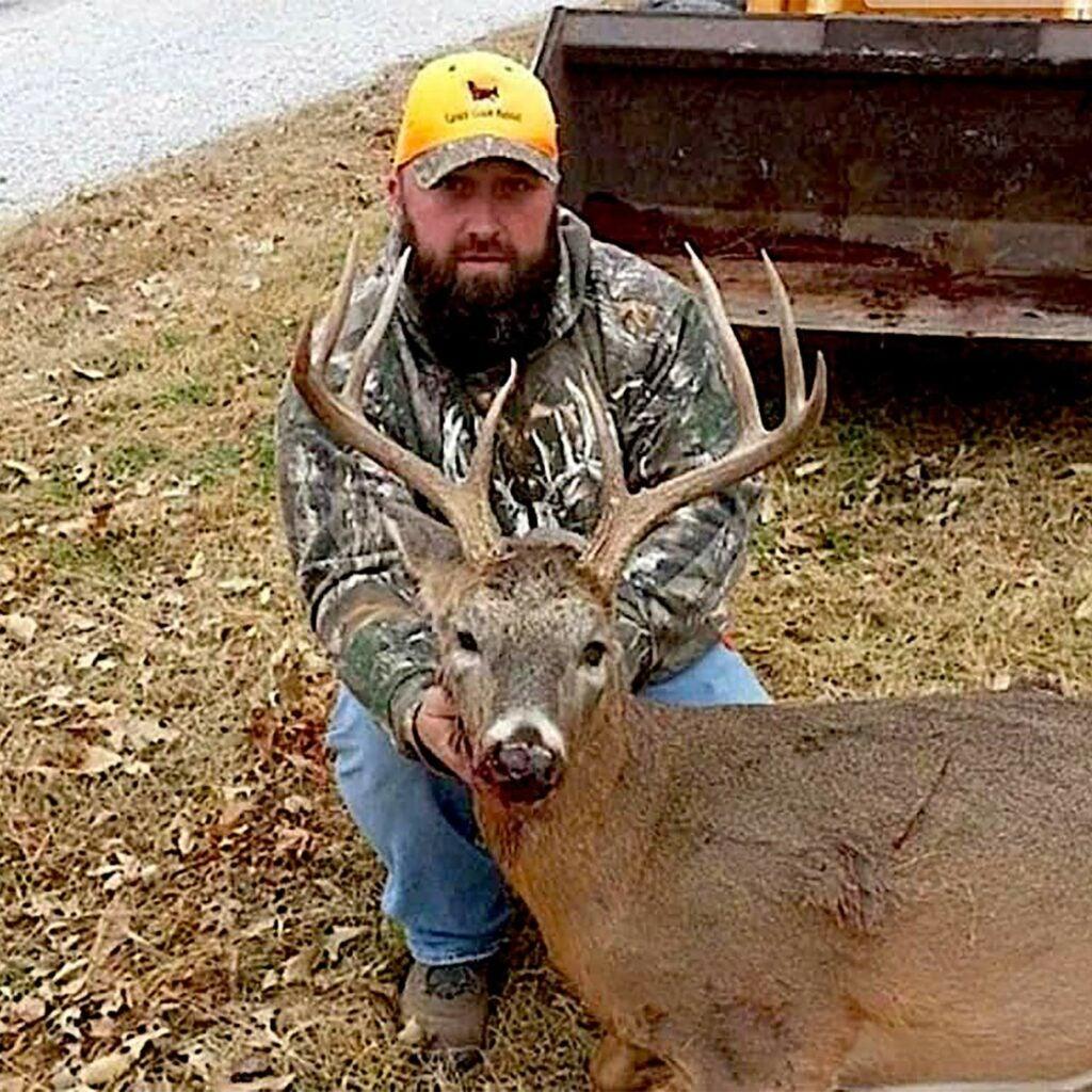 A hunter kneels beside a whitetail deer.