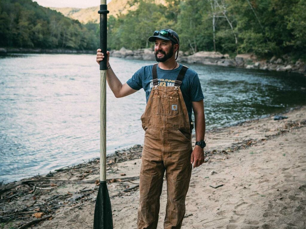Angler standing on a sandbar with an oar.