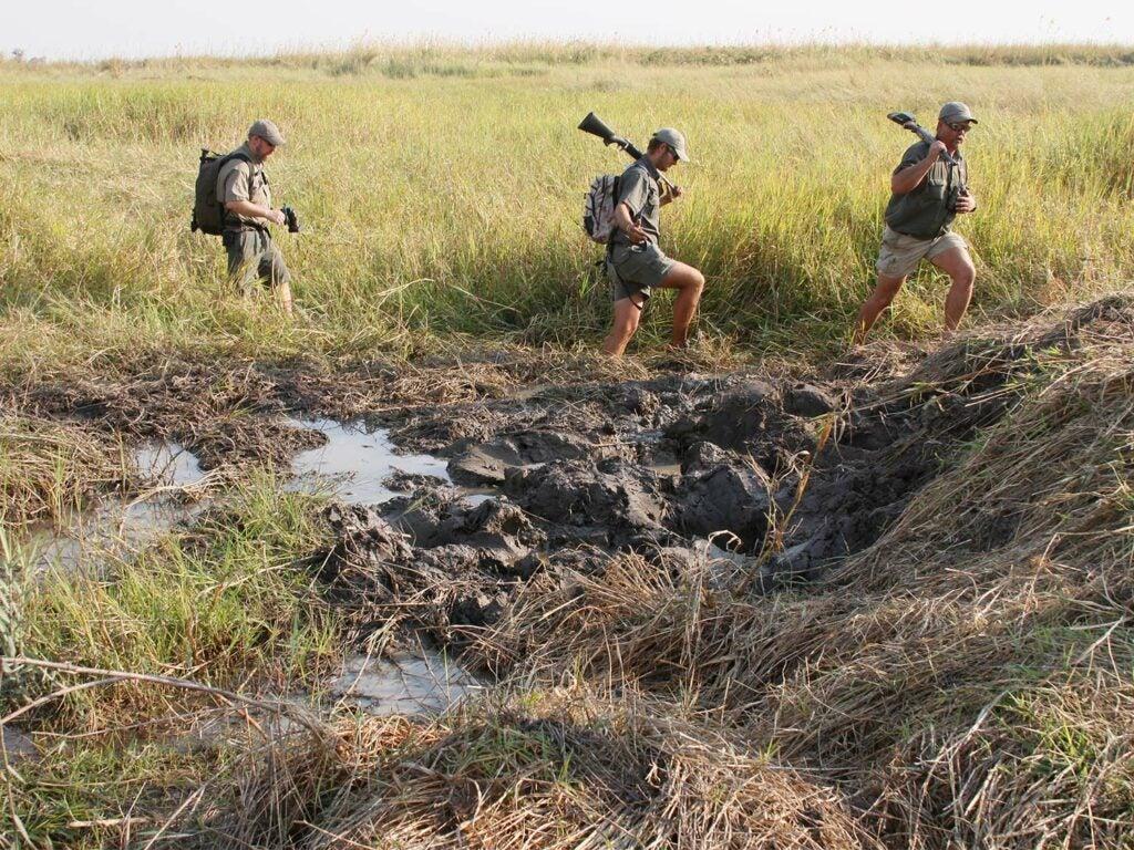 Hunters trek through the mud in Africa.