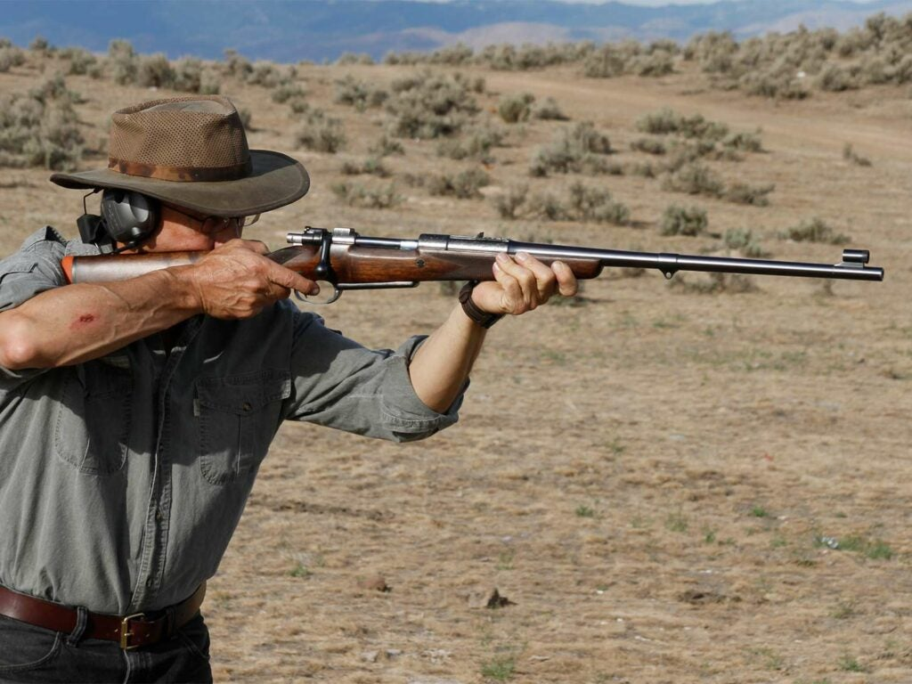 A hunter aims a rifle on an African plain.