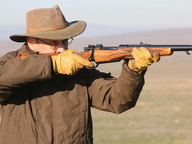 A hunter aiming a CRF Mauser rifle.