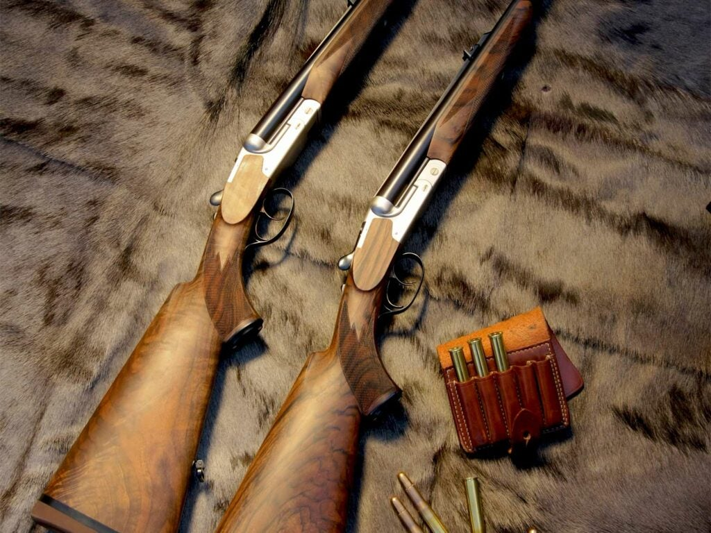 Two hunting rifles on a pelt with ammo beside them.