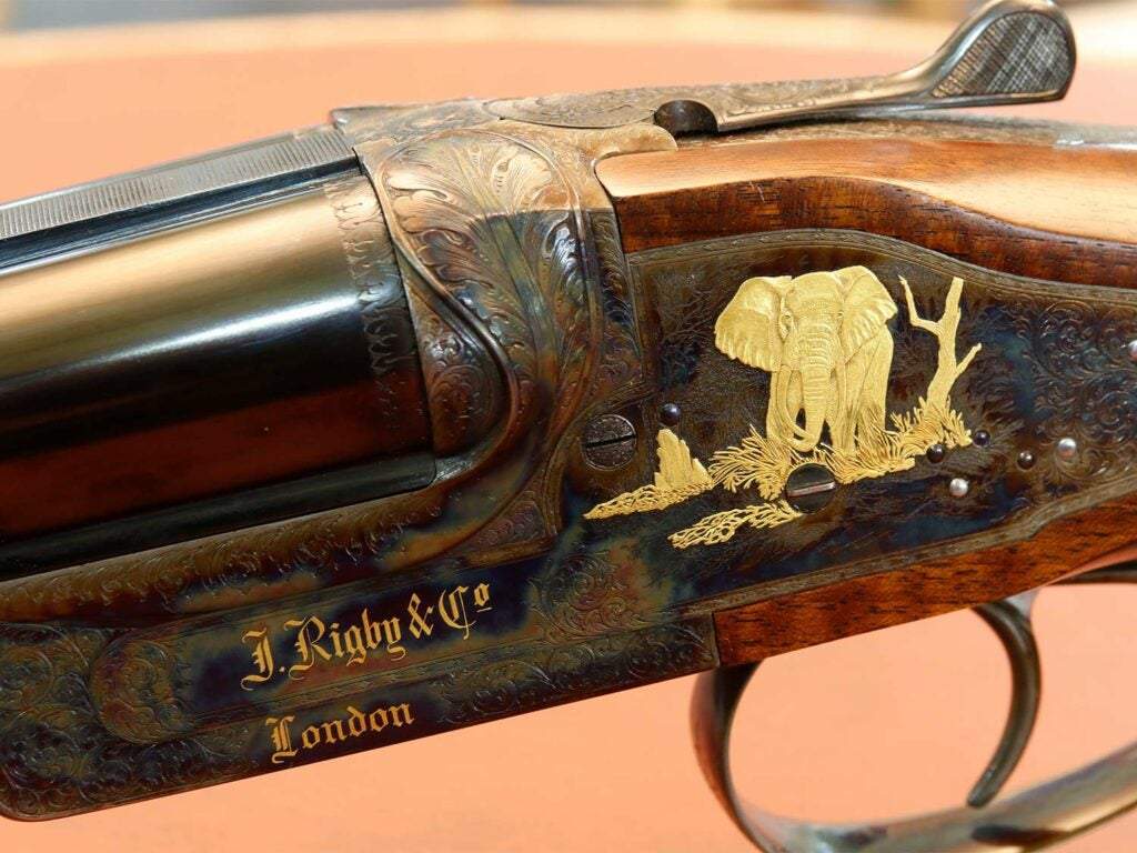 Closeup detail of a rifle stock showing custom engraving and an elephant inlay made of gold.
