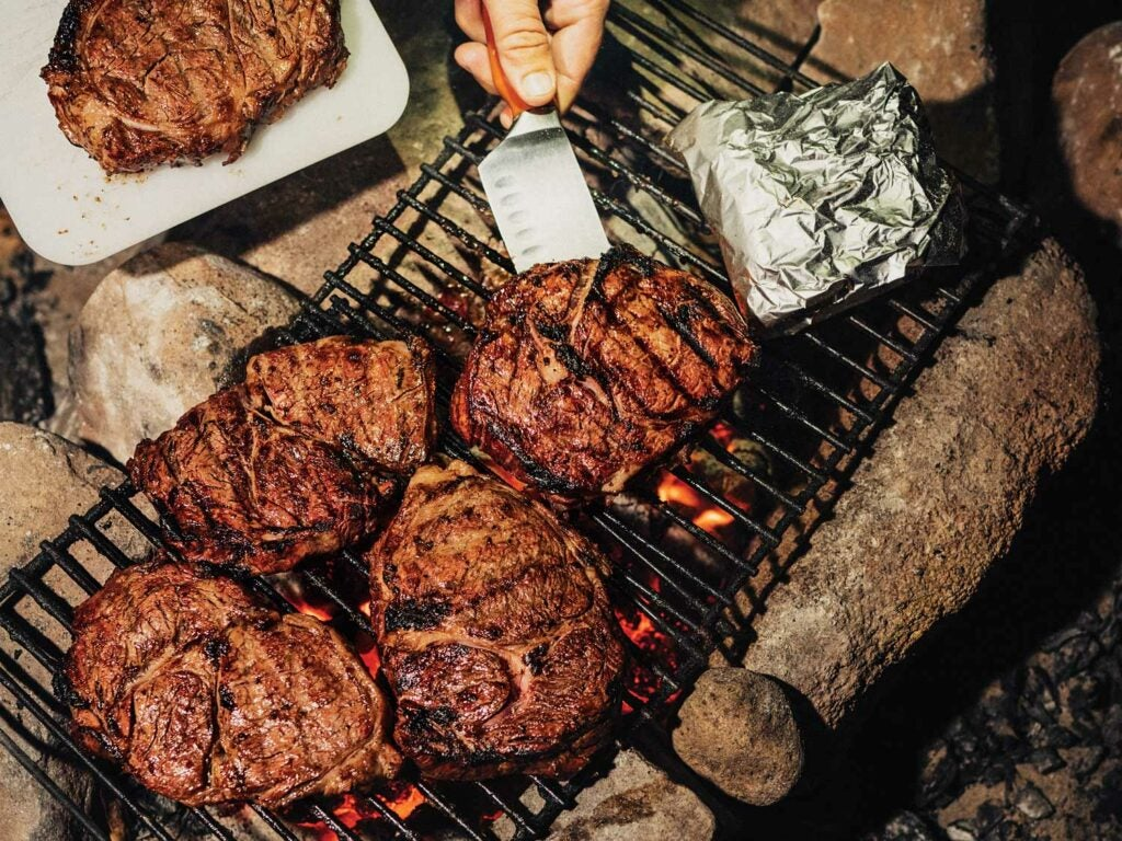 Steaks on a campfire grill.