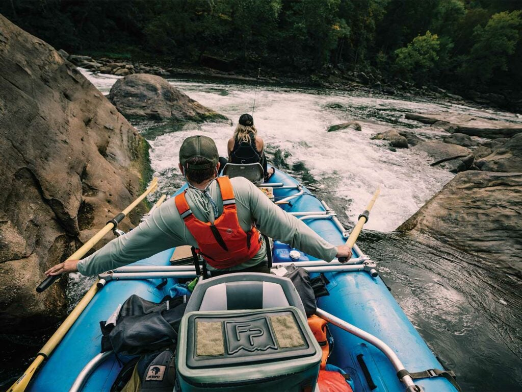 Anglers rafting down a river.