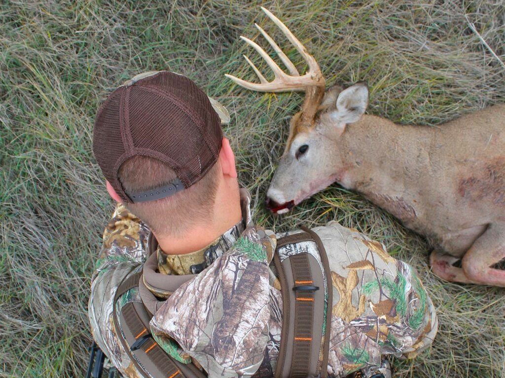 A hunter sits next to a whitetail deer that's dead on the ground.