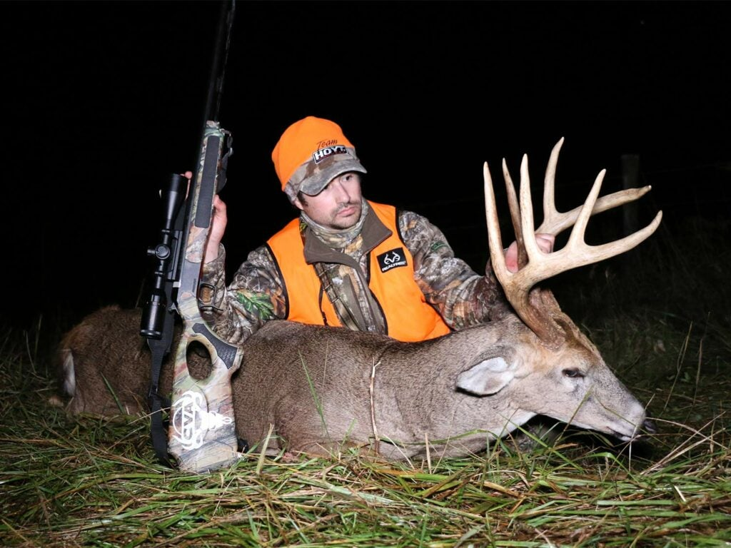 A hunter sits next to a whitetail deer and holds its head by the antlers.