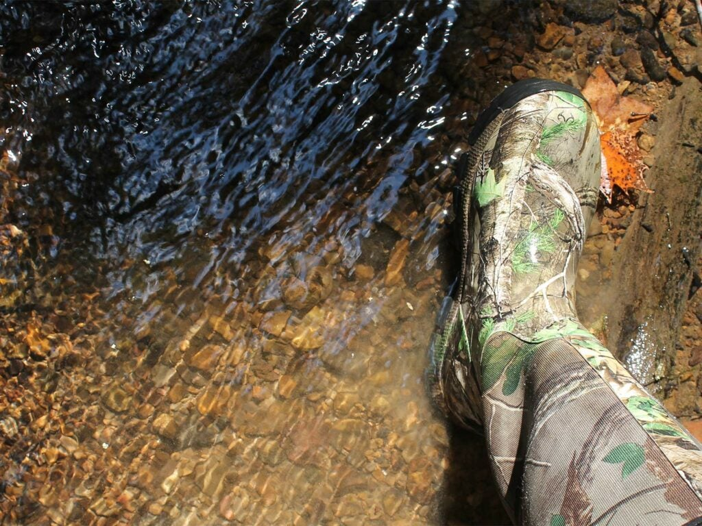 A hunters foot in wading boots is next to water.
