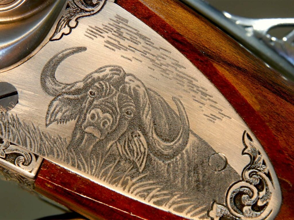 Close up of a rifle stock custom engraved with a cape buffalo metal plate.