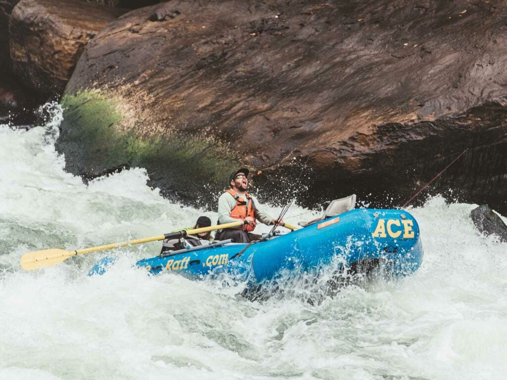 Man whitewater rafting down a river.