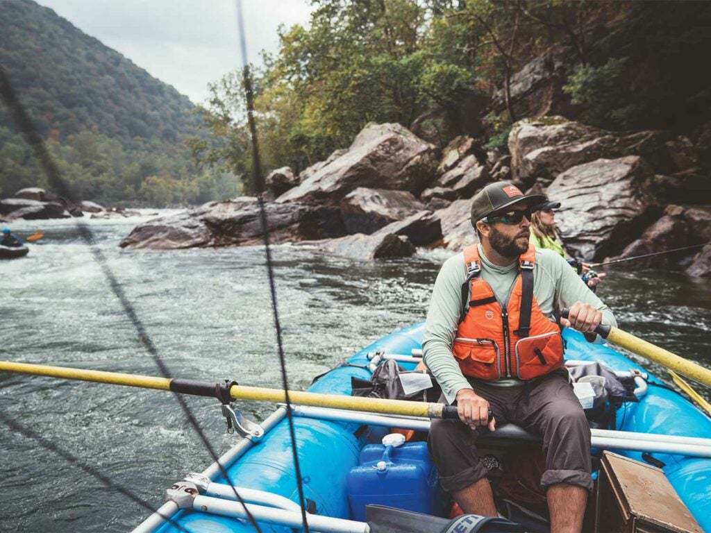 Anglers whitewater rafting down a river.