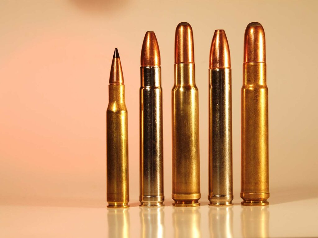 A lineup of hunting rifle cartridges standing on a table.