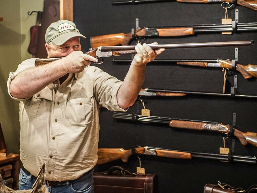 A man holds up a shotgun in a store.