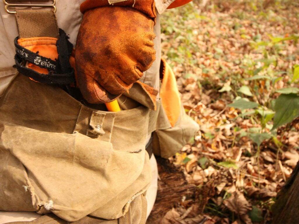 A hunter reaches into their pocket for a shotgun shell.