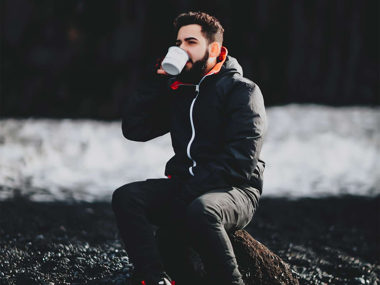 A man sits in the woods and drinks coffee.