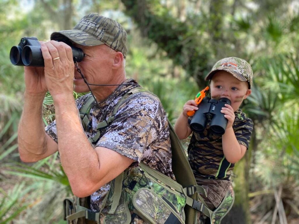 A hunter and child in the woods using binoculars.
