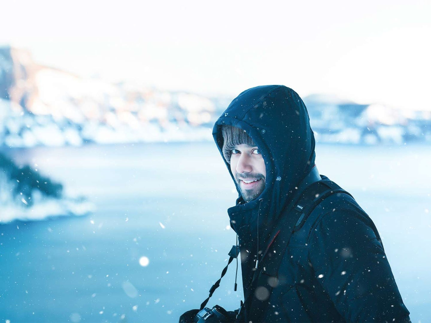 A bearded man wears a parka and stands in front of a snowy backdrop.