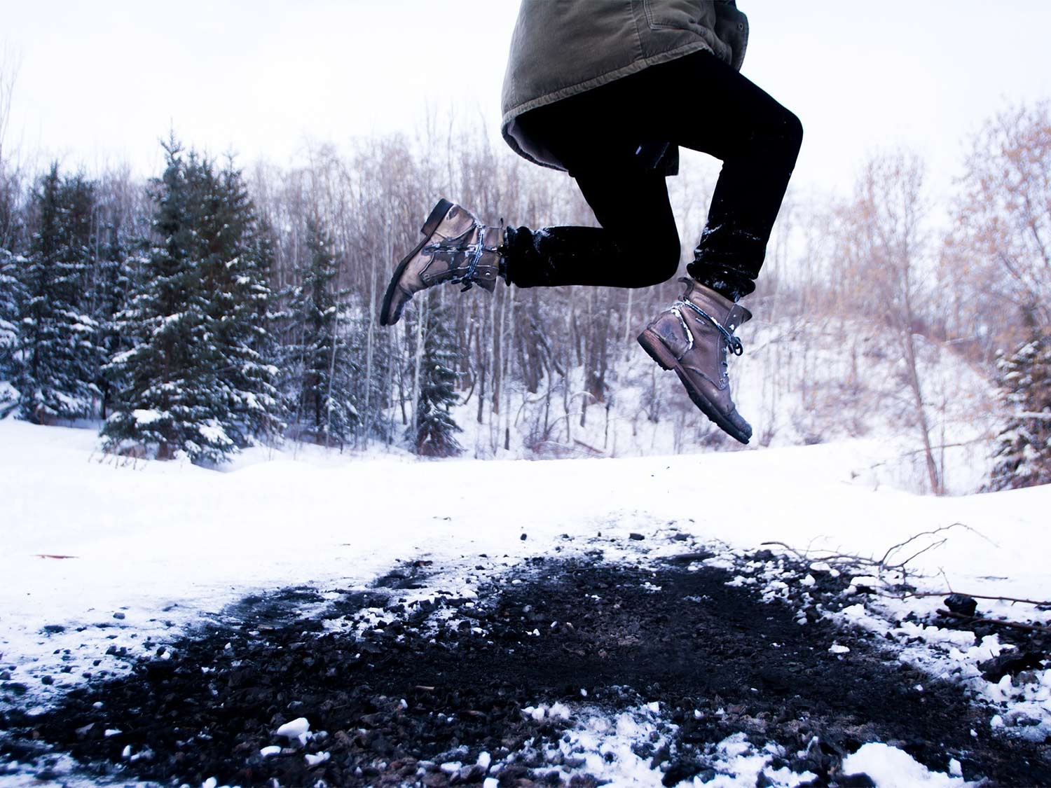 A woman wearing shoes leaps around in the snow.