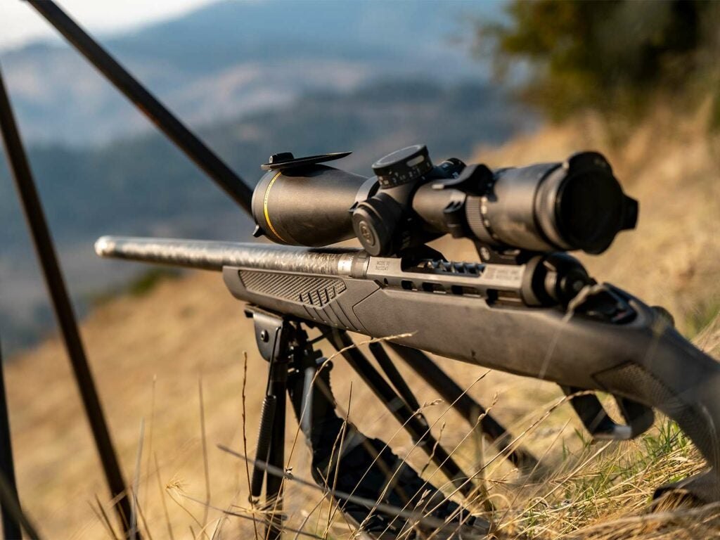 A rifle propped up on shooting sticks on a hillside.