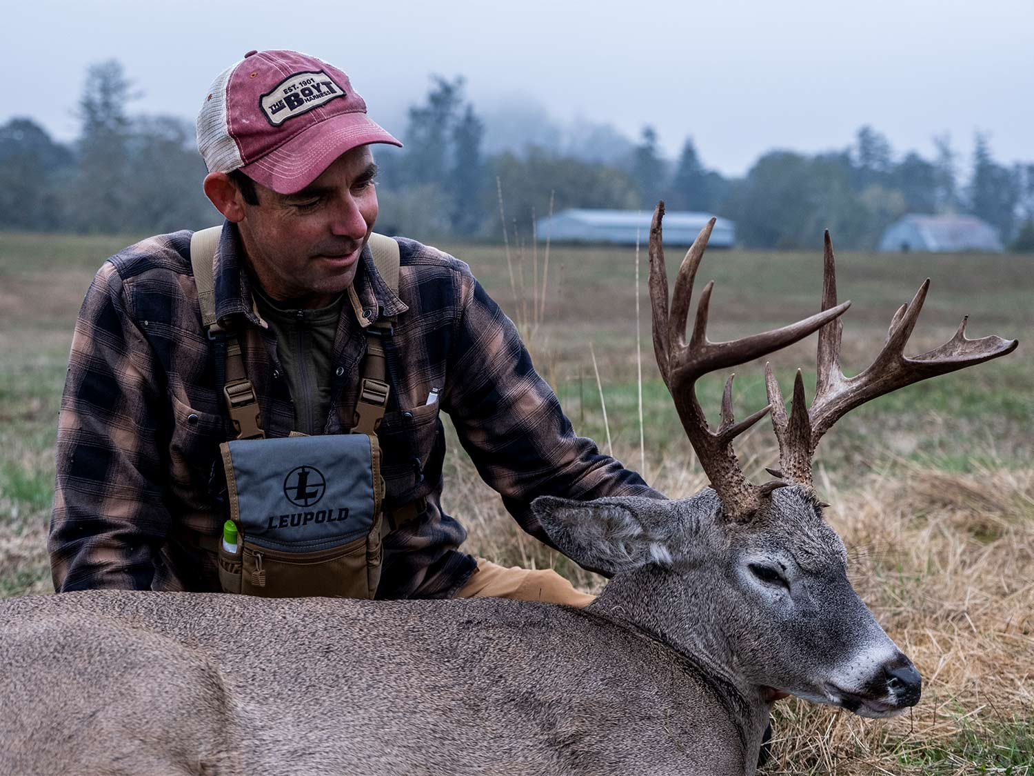 A hunter kneels behind a deer and holds its head up by the antlers.